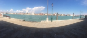 A panoramic view across the Giudecca Canal from the shadow of the loggia.