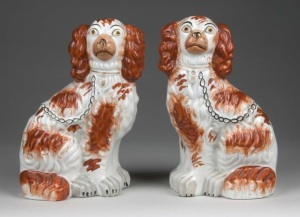 A pair of highly decorated Staffordshire dogs.
