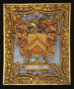 The coat-of-arms of the Rev. Thomas Whitehurst. (Credit: The Fitzwilliam Museum) Picture worked in rolled paper (red, blue and white with gilt edges), in the centre of which are the arms of the Rev. Thomas Whitehurst surrounded with foliage and flowers on a light blue grosgrain background. Below are the initials TW and the date 1699. Light blue grosgrain background probably added in the early 19th century. Framed in 1832. C.1699