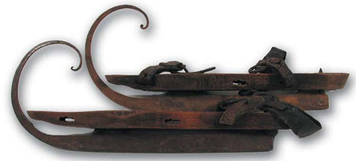 Late ninteenth-century wood and metal skates with an elaborate upward curl at the front of the blade.